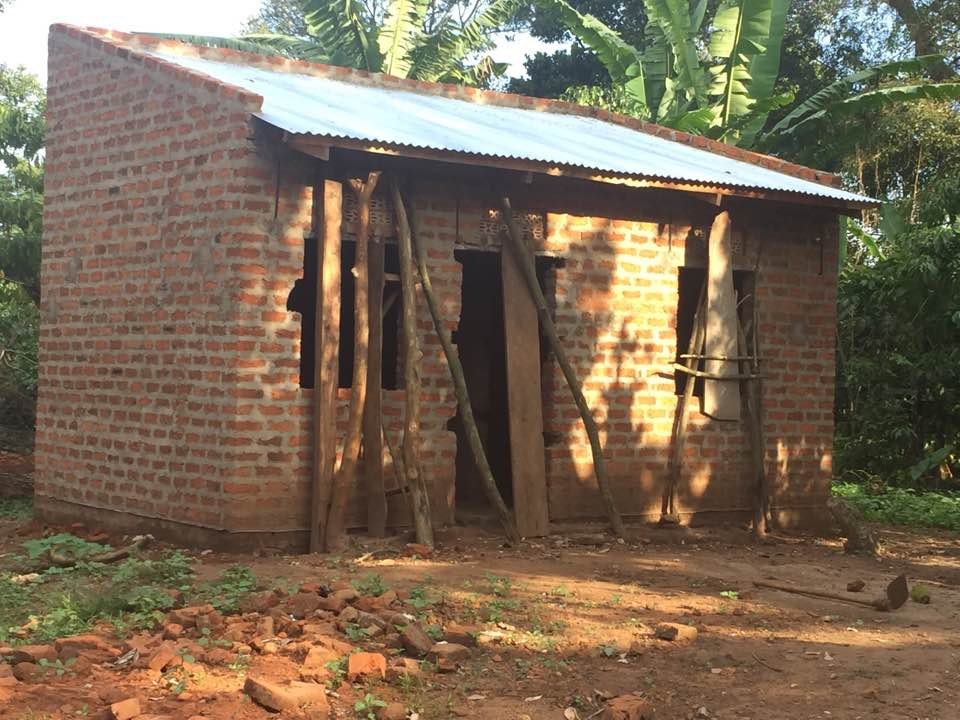 12- Sarah Tibagonsega 2017 new home nearly complete sticks cover windows to keep animals out until window shutters are installed.jpg