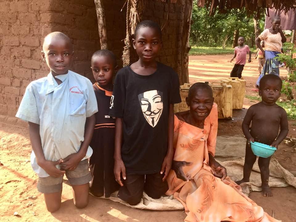 12- Granny Sarah Tibagonsega 2017 with her 3 grandchildren so grateful for her new home.jpg