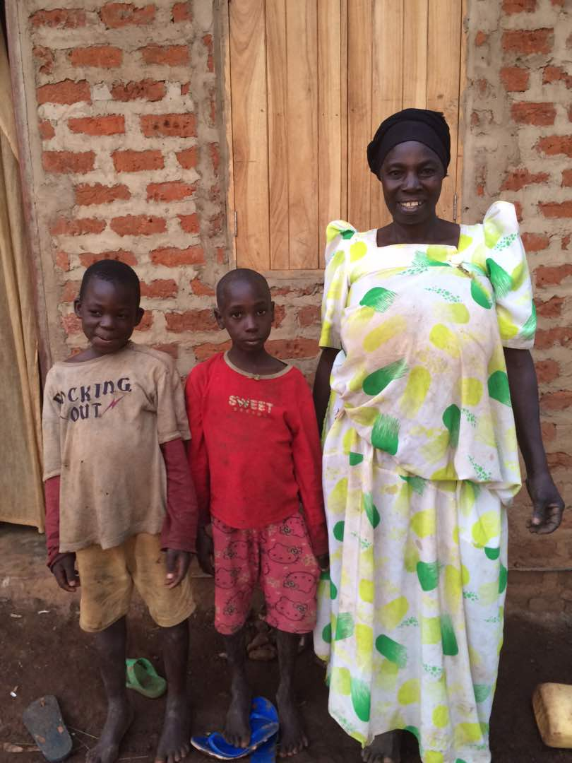 12 Margaret Nabatanda and family in front of new home.jpeg