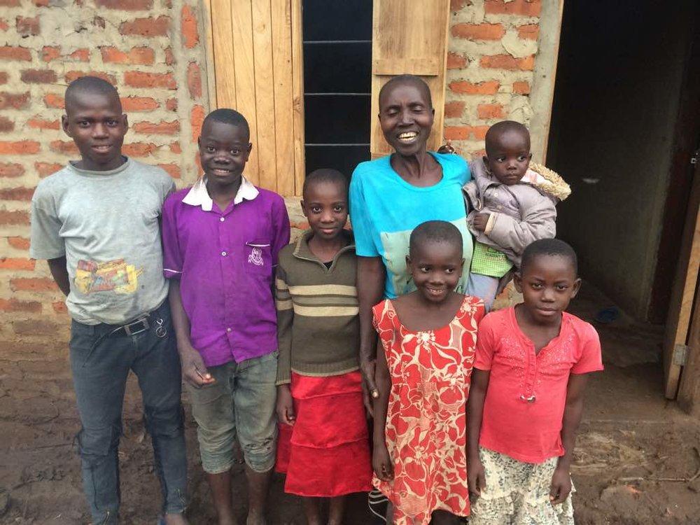 7 Sarah Namugaya and family in front of their new home .jpeg