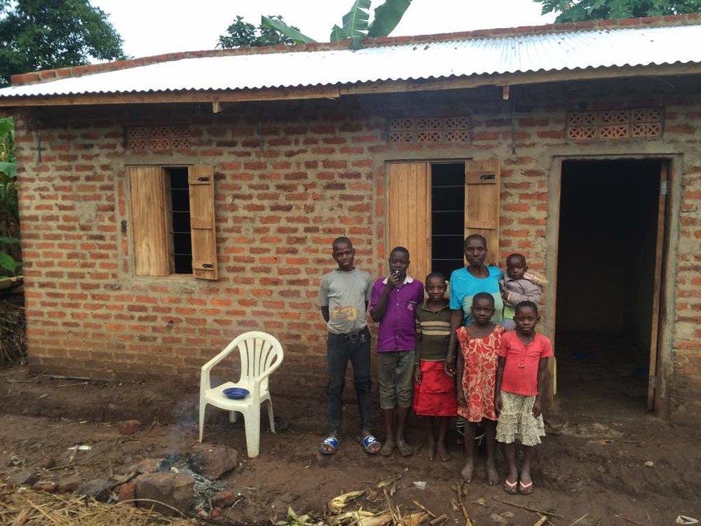 7 Sarah Namugaya and family in front of new home .jpeg