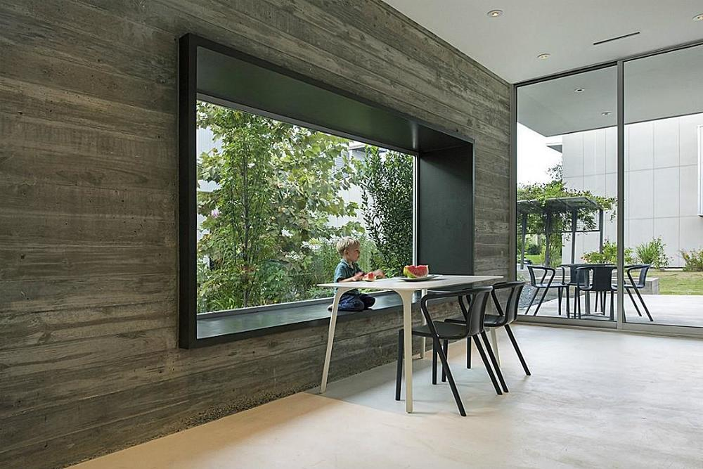 Breakfast area stretches outward with bespoke steel window in cast in place concrete wall and outdoor terrace off to side.