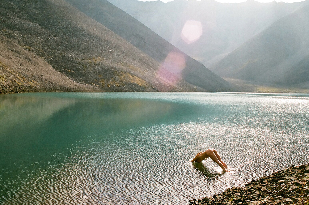 A swimmer imitates the shape of the mountains in Yukon. Shot by Hallie Herz