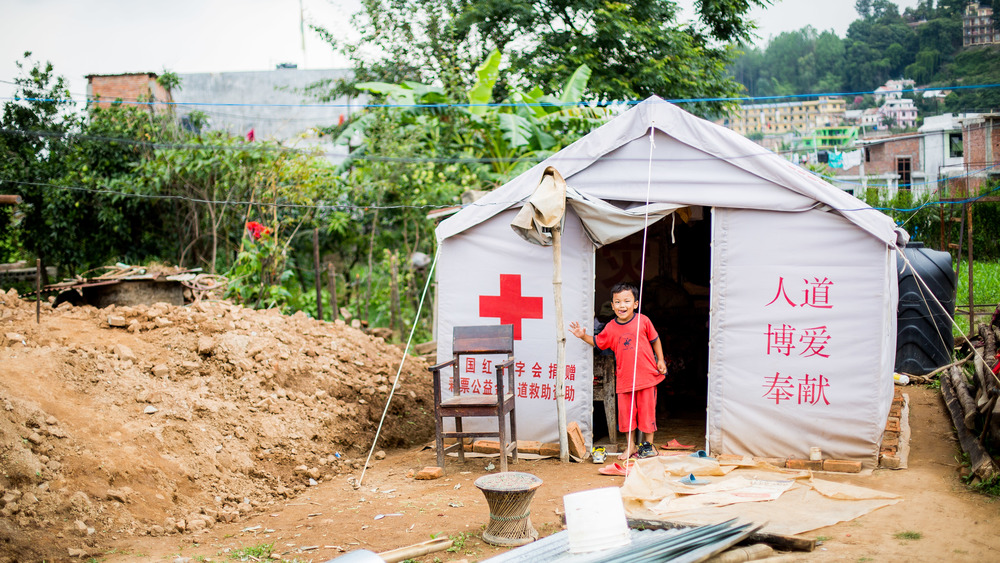 Little boy living with his parents in their temporary house this time provided by the Chinese Red Cross.
