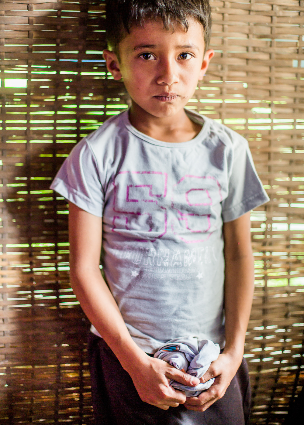 Posing with his new shirt in one of the temporary shelters made from bamboo with plastic sheeting for a roof.