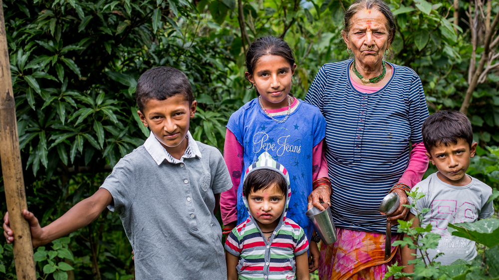Group of children with their grandmother wearing new clothes provided by Micro-Care Nepal Foundation.