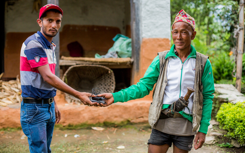 Rohit handing over a telephone to local man who couldn't afford to buy one. Now he can keep contact with his family and friends in the city or in other remote parts of Nepal.