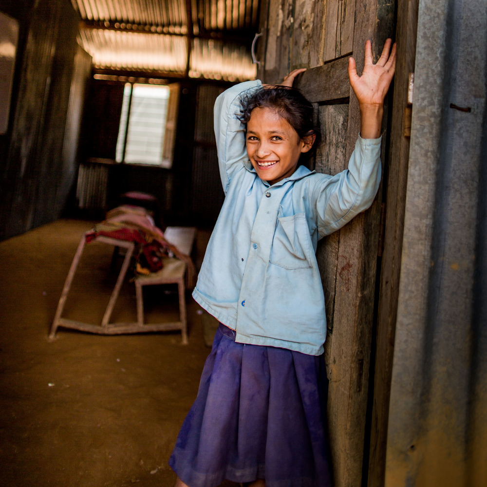 Girl posing in front of her classroom.  The school benches in the background, twisted by the destructive force of the earthquake, are in need of some maintenance.