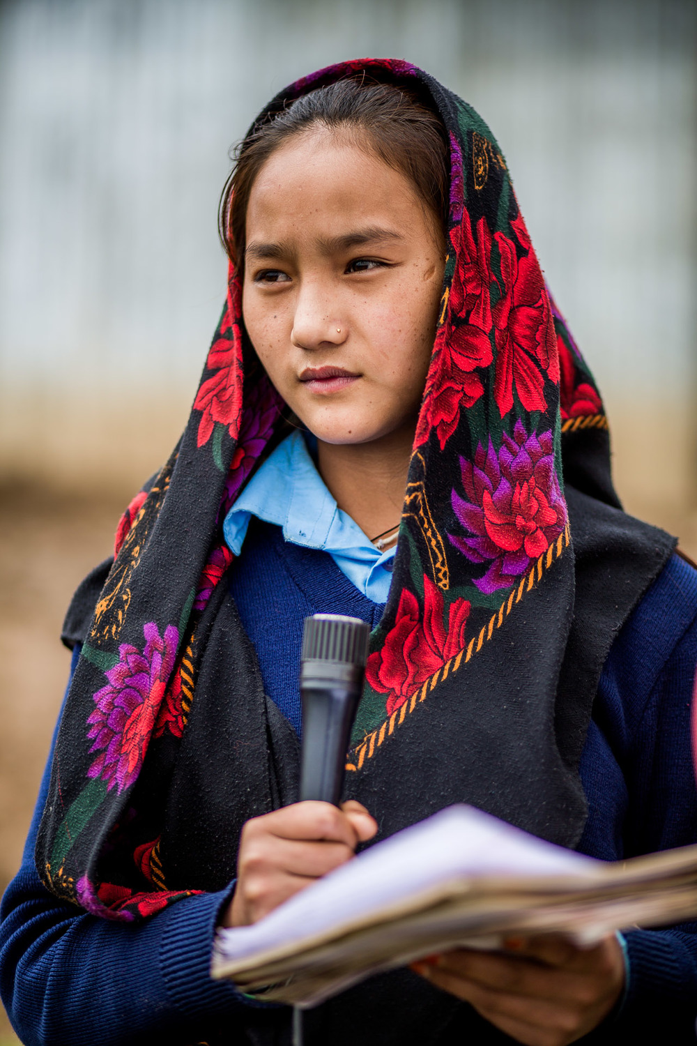 Girl reading her schoolwork as part of the morning assembly to the other 200 students.