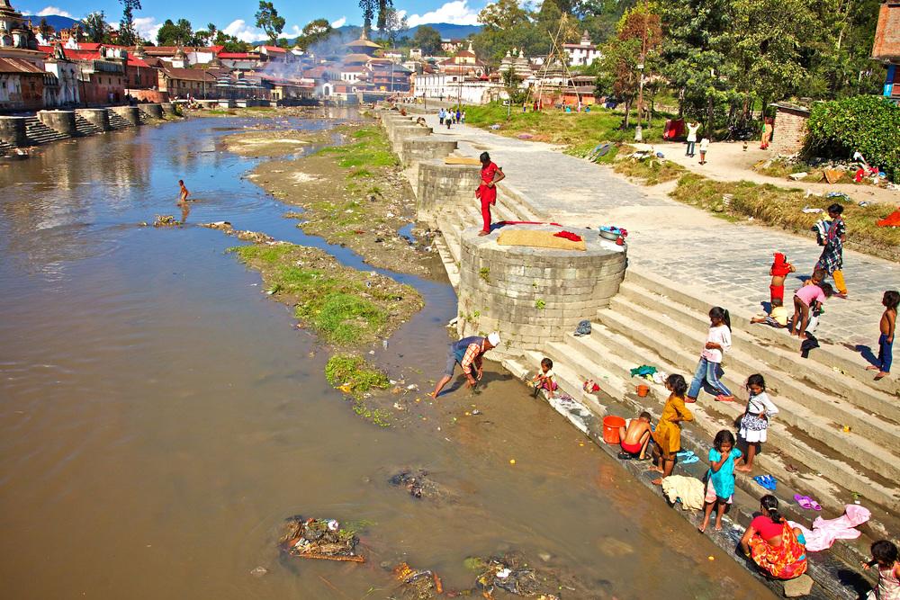 De rivier bedding van de heilige Bagmati rivier met in de verte de Pashupatinath tempel waar de Hindoeïstische crematies plaatsvinden.