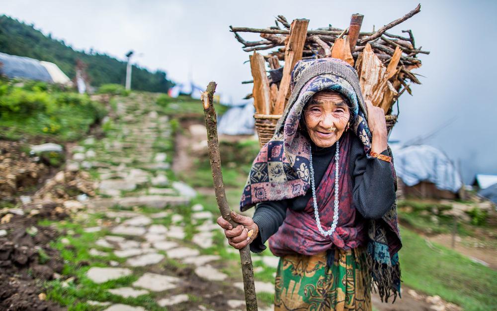 Bewoonster van Laprak komt met een grote mand vol hout terug uit het bos om haar vuur opnieuw te laten branden. zodat er gekookt kan worden en men warm blijft.