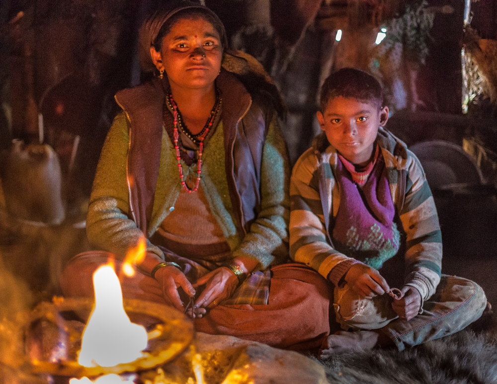 Sumit and his mother siting by the fire. This is the place where they prepare food, eat and sleep.