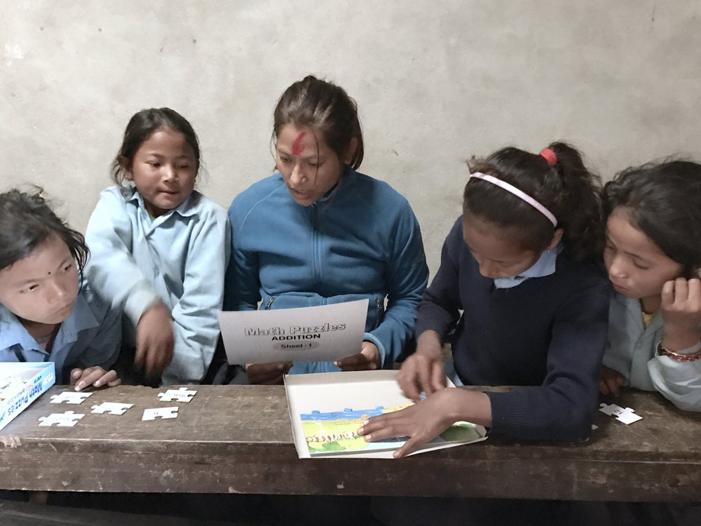 Teaching together with local teachers to introduce and learn them how to use the school materials provided by Micro-Care Nepal.