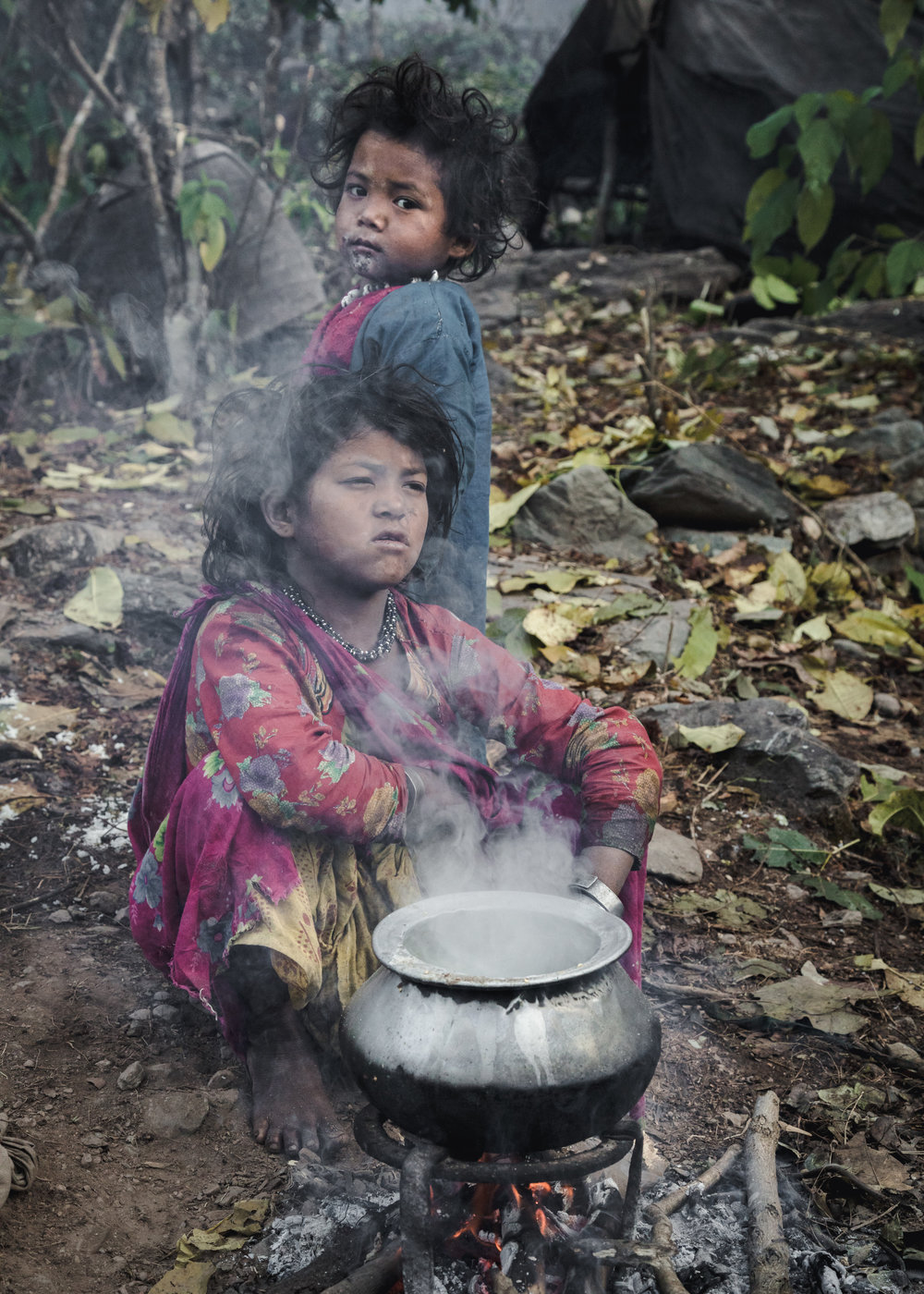 Children preparing their rice on a small fire.