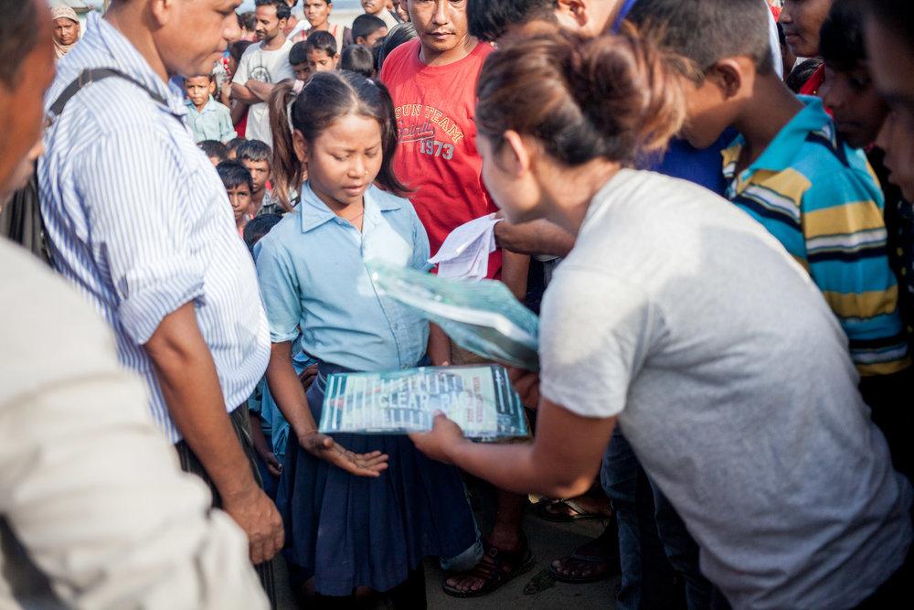 Samjhana deelt schoolmaterialen uit aan de kinderen.