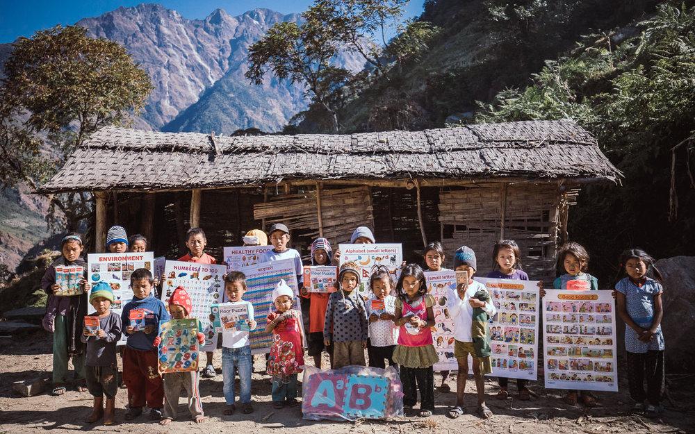 Kinderen laten hun nieuwe schoolmateriaal zien in een klein dorpje van het afgelegen Arun gebied.