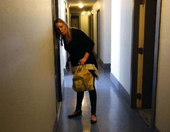 Lori delivering meals to a resident at the Raman Hotel. Photo curtesy of Leah Millis at The Chronicle.