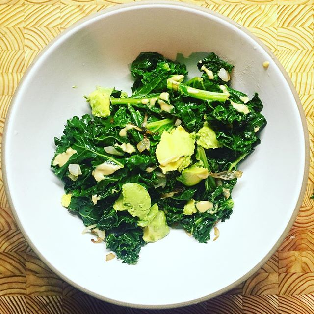 Whipped up a quick warm kale salad 🌿 I normally remove the stems but I didn't have much time so I chopped everything up. I started by melting a tablespoon of coconut oil in a medium pot, sautéed an entire chopped #shallot and a pinch of salt + added the kale and covered the pot for a few minutes. Move to a bowl, add avocado and a dollop of #tahini and you've got a #10minute #vegan meal 👏👏 Make two heads of kale next time to fill up the bowl 😉