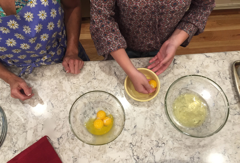 Tiffany, in daisy apron, watches as her 12-year old daughter Haley masters the art of egg separating