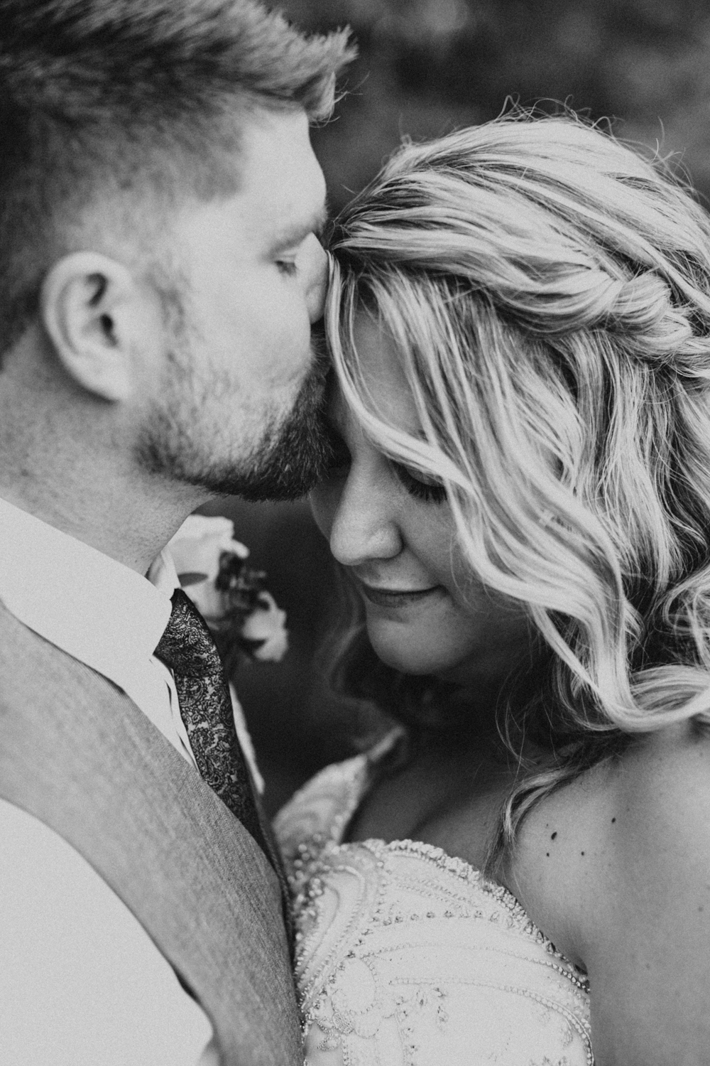 Groom kisses Bride on the forehead in sweet black & white wedding portrait.