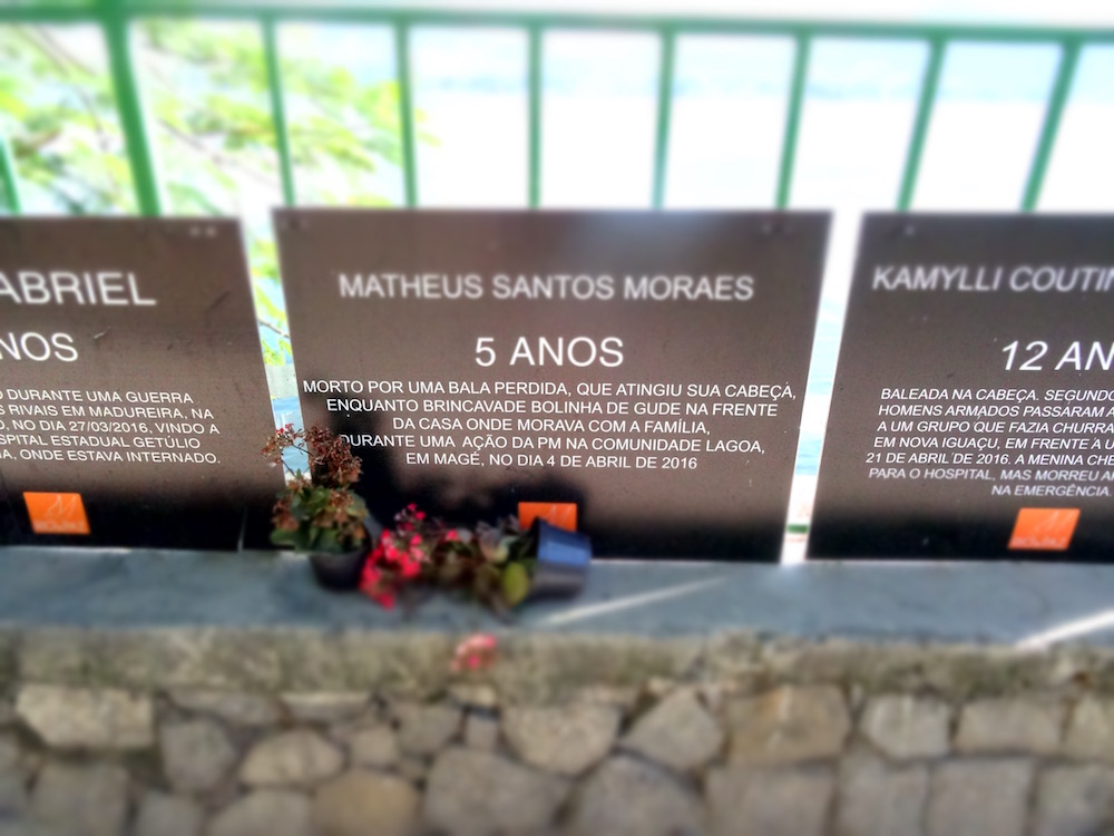 """Matheus Santos Moraes - 5 years old - Killed by a stray bullet that hit him in the head while he was playing with marbles in front of his home where he lived with his family, during a military police raid in the lake community in Magé on the 4th of April 2016""  One of many signs hung along Lagoa Rodrigo de Freitas bringing awareness to the city's struggle with violence. Over 2000 people were killed through violence in Rio between January and April of 2016 alone, many of whom were children and innocent bystanders who got caught in the cross fire between drug lords, gangsters and the military police."