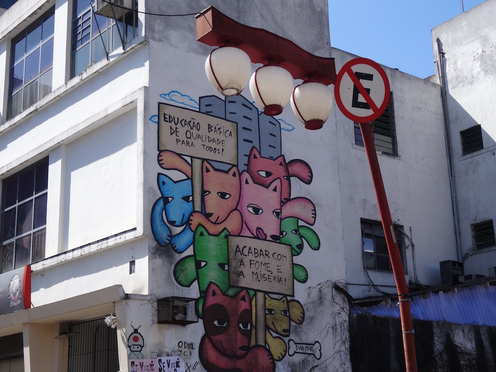 "Liberdade - the Japanese precinct in São Paulo. Japanese 'lanterns' for street lights and street art. ""Basic quality education for everyone!"" "" End hunger and misery"""