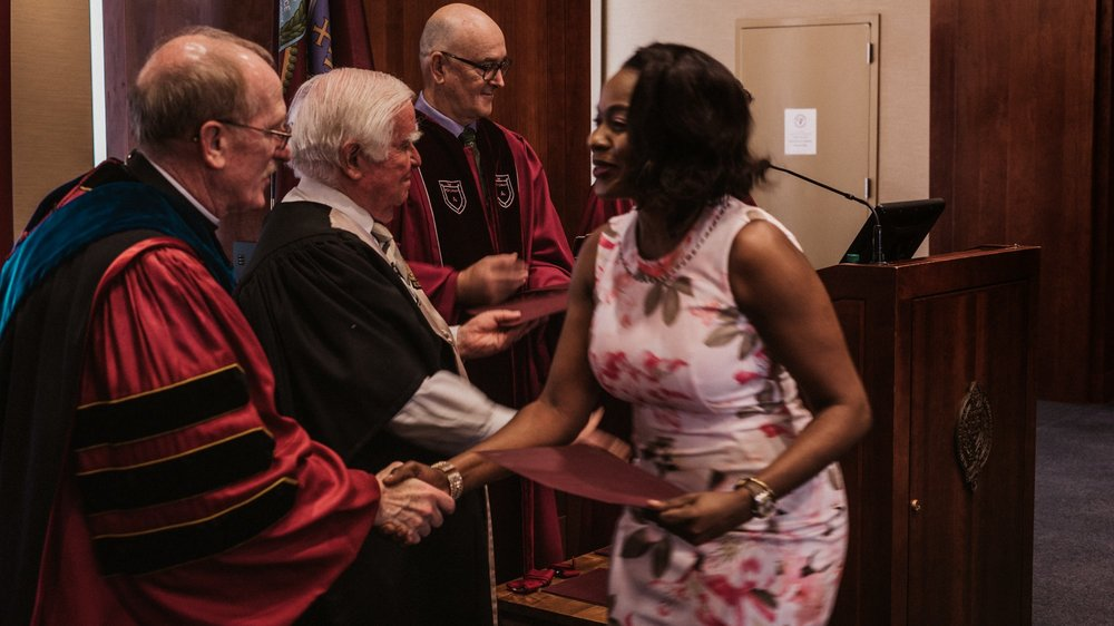 IDHA 52 Graduate Vena Semaitre shaking the hands of Rev. Joseph M. McShane, S.J. at IDHA Graduation.