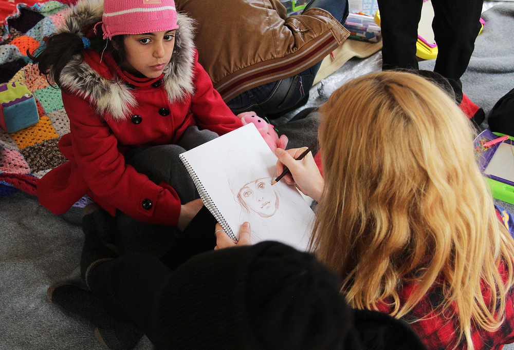 Aubrey Roemer drawing portraits at Children's Protection Play Center at Refugee Camp Moria, 2015. Photo courtesy of Bob Miller.