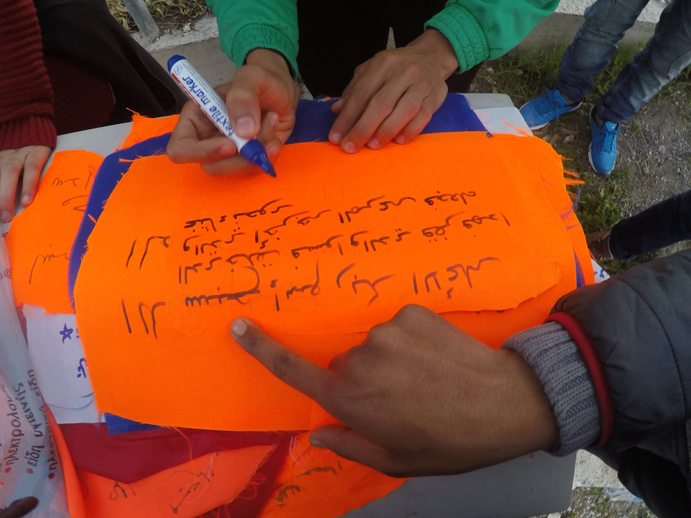 Refugee men writing prayers and protests on life jacket swatches outside of Refugee Camp Tae Kwon Doe, in Athens, 2015. Photo courtesy of artist.