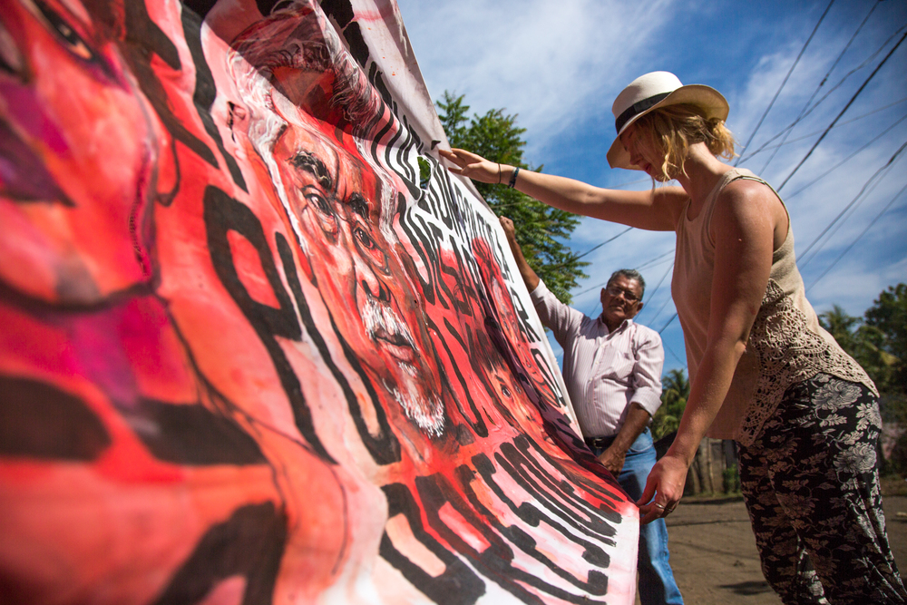 Artist Aubrey Roemer and La Isla Foundation cofounder, Juan Salgado, looking at a painted protest banner in Chichigalp, Nicaragua, 2015. Photo courtesy of Tom Laffay.