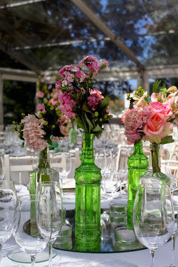 Reusing glass bottles for the wedding table decor in Portugal.JPG