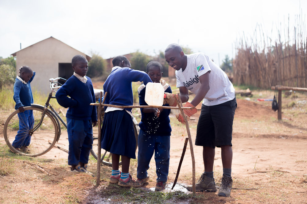 A local volunteer helping the school children use a tippy tap, a self made tap for washing hands