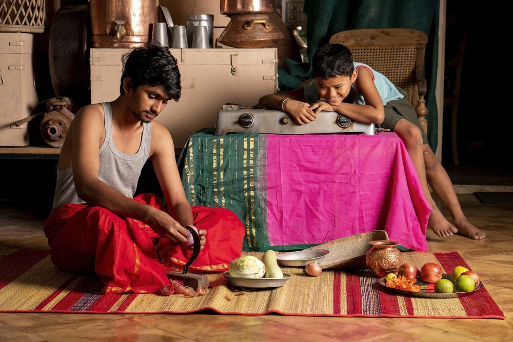 A young man slices vegetables while his friend watches.