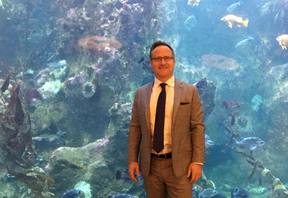 Above: Dean Jones, President & CEO of Realogics Sotheby's International Realty, stands in front of a massive aquarium that served as a dramatic backdrop during the panel discussion.