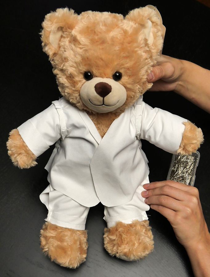 It is much easier to adjust the length of your sleeves with the jacket on your bear, like so.