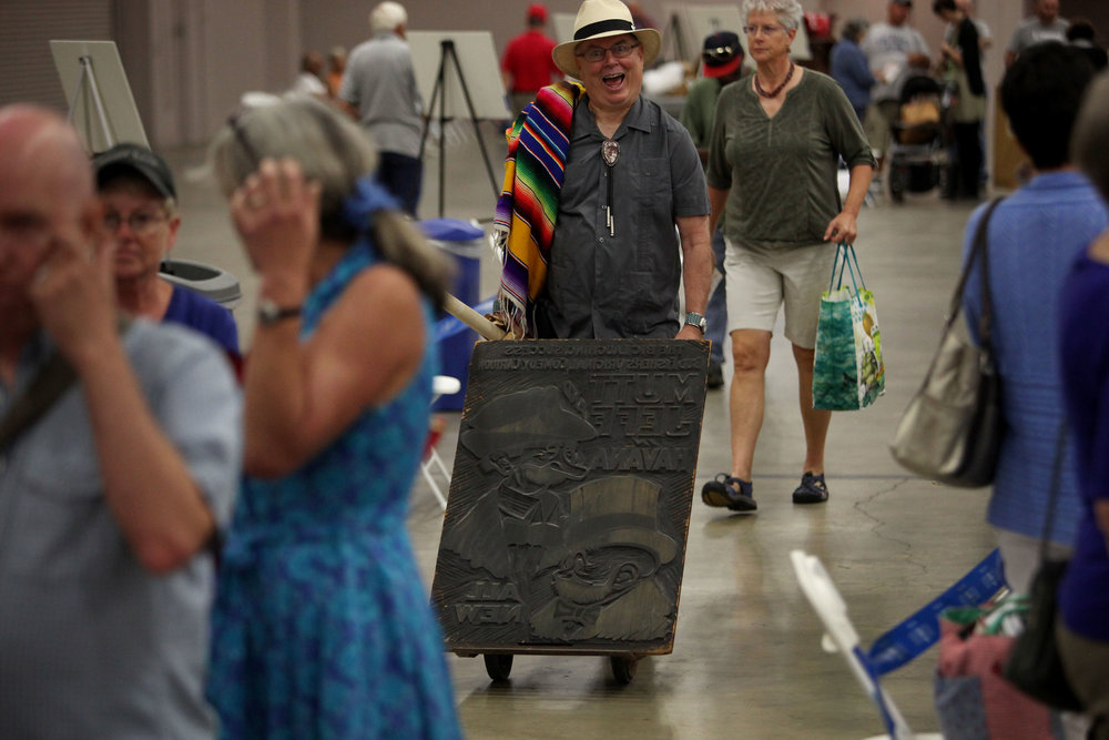 "Bill, of Gallup, rolls his antique movie poster wood cut down the line at Antiques Roadshow at the Albuquerque Convention Center, July 19, 2014, in Albuquerque NM. The poster was for the early 1900s movie ""Mutt and Jeff in Havana."" (Morgan Petroski/Journal)"