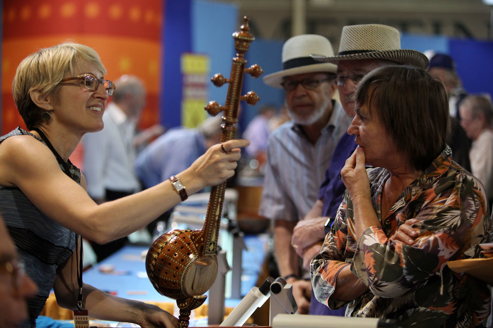 At left, Martha Blackwelder looks over an instrument owned by Gloria, of Albuquerque, at right at the Antiques Roadshow at the Albuquerque Convention Center, July 19, 2014, in Albuquerque NM. Gloria believed the instrument to be of Chinese origin and was surprised when Blackwelder told her the instrument was from India. (Morgan Petroski/Journal)