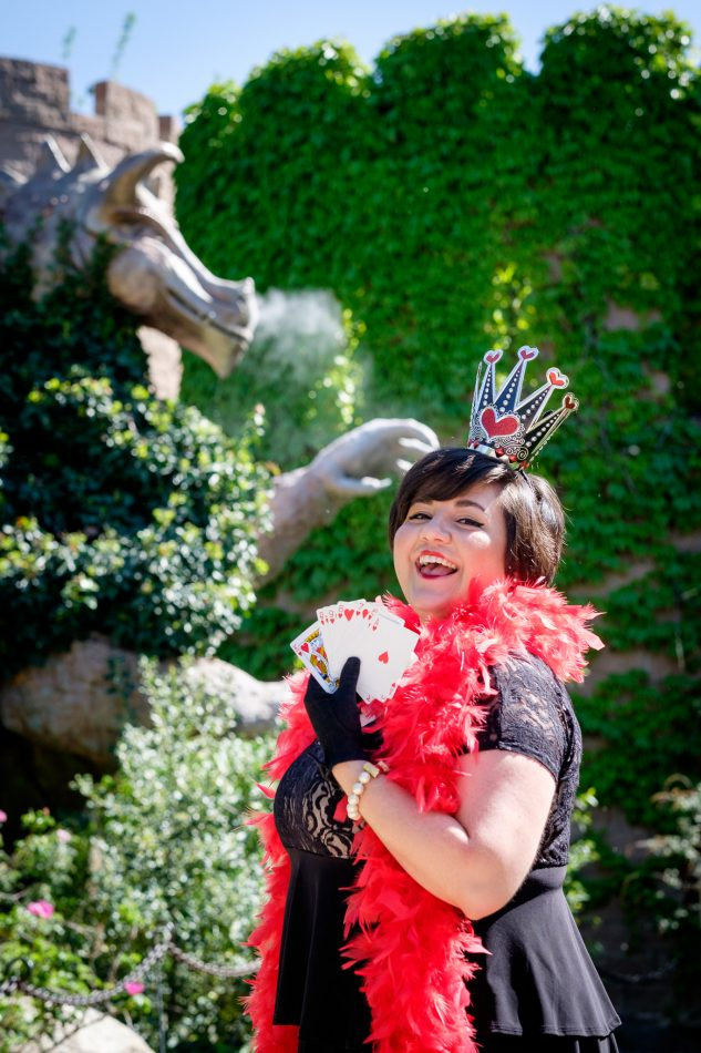 woman dressed as queen of hearts with cards and dragon