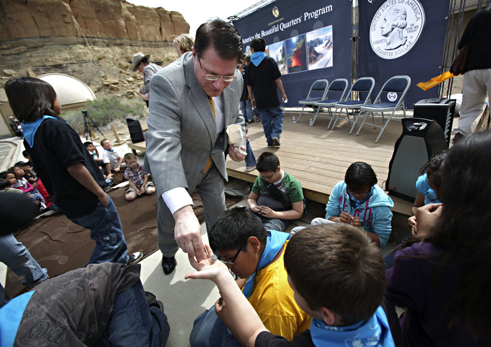 Deputy Director of the United State Mint Richard Peterson hands out Chaco Canyon quarters to 5th graders from Apache Elementary during the quarter launch at Chaco Canyon, Thursday, April 26, 2012. (Morgan Petroski/Albuquerque Journal)