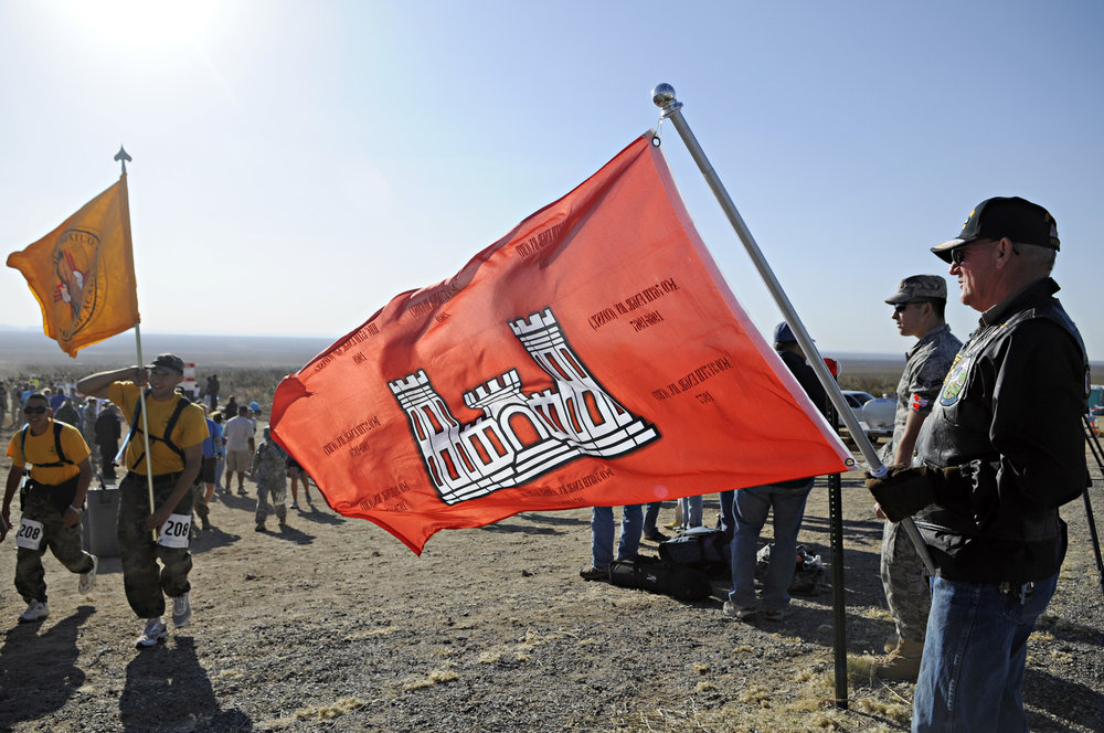 Vietnam veteran Bruce Fonnest, at right, holds up the Engineer flag as walkers and runners pass by at water station 3 during the 22nd Annual Bataan Memorial Death March at White Sands Missile Range, Sunday, March 27, 2011. (Morgan Petroski/Albuquerque Journal)