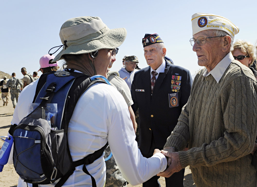 Bataan survivors Harold Bergbower, 90, from Peoria, AZ, at right, and William Eldridge, 88, from Citrus Heights, CA, greet runners at water point 7 during the 22nd Annual Bataan Memorial Death March at White Sands Missile Range, Sunday, March 27, 2011. (Morgan Petroski/Albuquerque Journal)