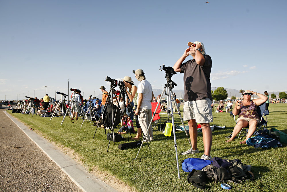 Second from the right, Cal Harr, from Centennial, CO, takes a look through his solar glasses while getting his camera set up to photograph the annular solar eclipse while taking part in the viewing party near the Hard Rock Casino Presents the Pavilion, Sunday, May 20, 2012, in Albuquerque, NM. (Morgan Petroski/Albuquerque Journal)