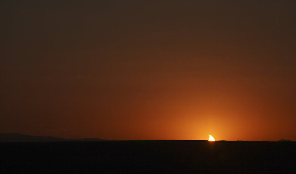 The setting sun appears like a shark fin as it dips below the horizon while completing the annular solar eclipse as viewed near the Hard Rock Casino Presents the Pavilion, Sunday, May 20, 2012, in Albuquerque, NM. (Morgan Petroski/Albuquerque Journal)