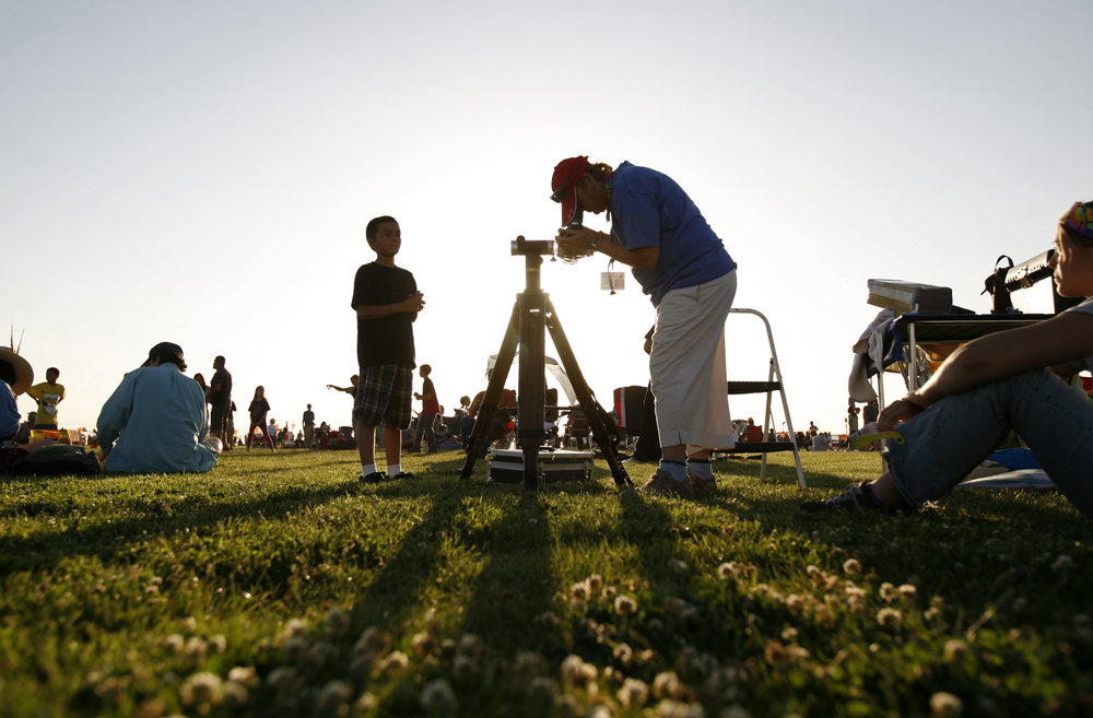 At right, Amy Estelle, with The Albuquerque Astronomical Society, adjusts the telescope, as Joseph Salazar, 9, waits to take a look at left, during the annular solar eclipse viewing party near the Hard Rock Casino Presents the Pavilion, Sunday, May 20, 2012 in Albuquerque, NM. (Morgan Petroski/Albuquerque Journal)