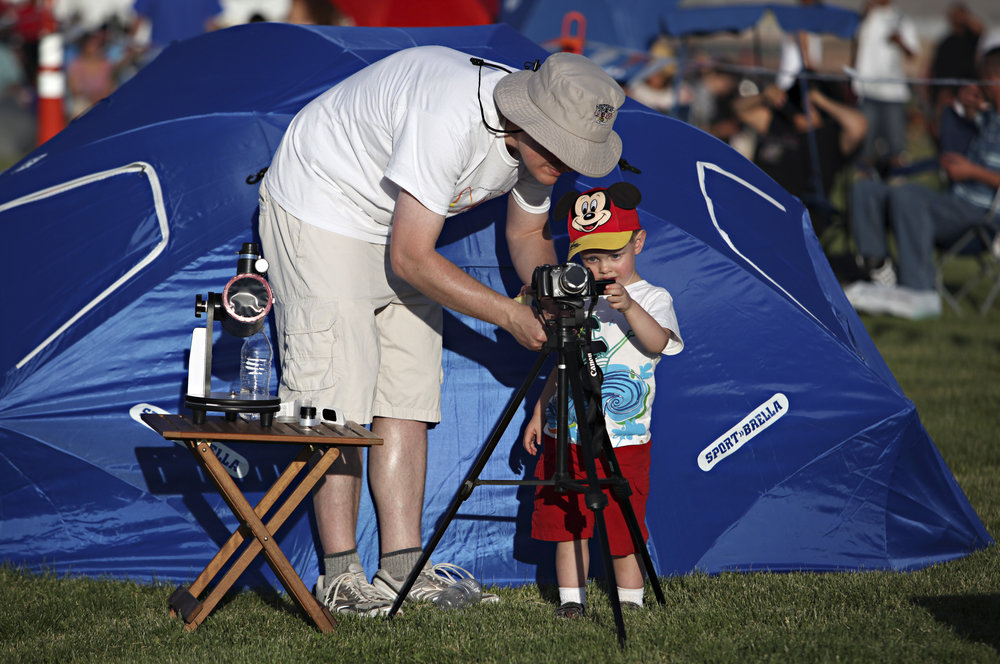 Gabriel Turner, 2, gets a little help from his father, David Turner, while viewing the annular solar eclipse during the eclipse viewing party near the Hard Rock Casino Presents the Pavilion, Sunday, May 20, 2012, in Albuquerque, NM. (Morgan Petroski/Albuquerque Journal)