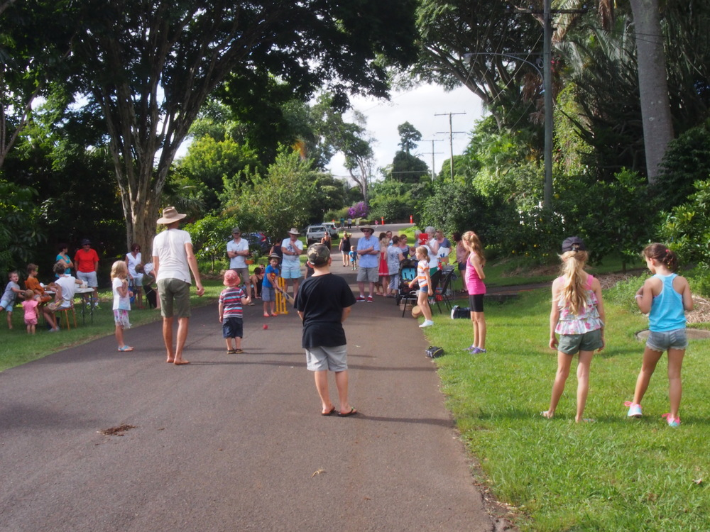 Kids play cricket in a traffic  calmed residential street.  Everyone gets a go.