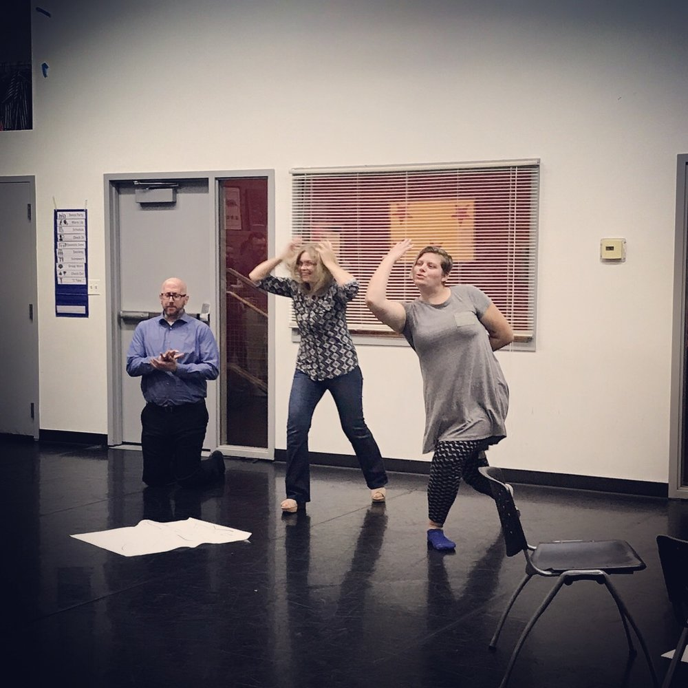 teaching artists Kaylie & Sean make a tableaux with Emily K's mom.