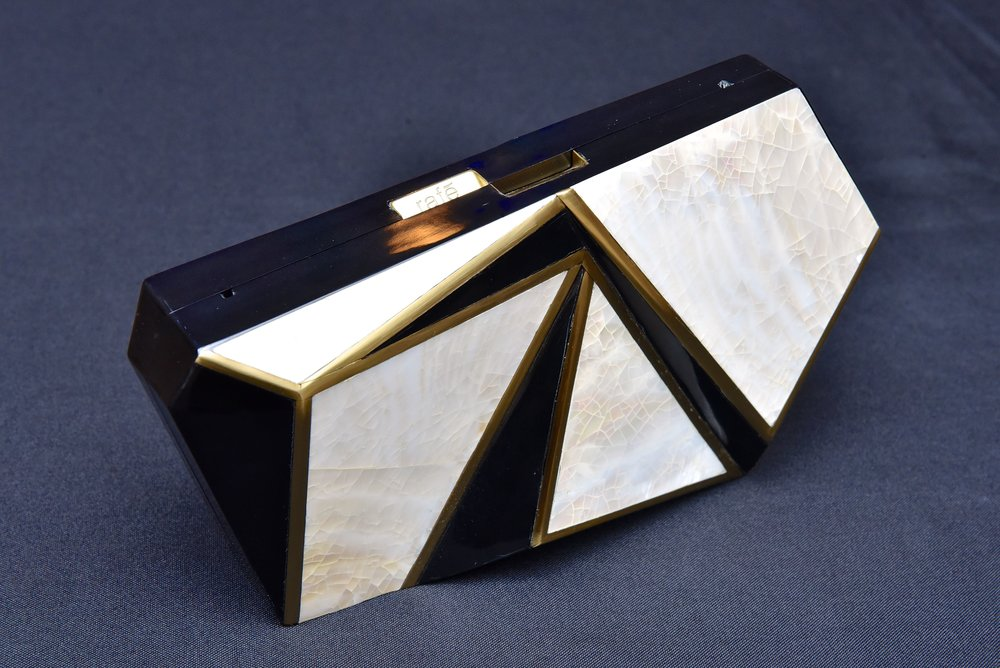 The Azura Faceted Minaudière in black and white shell inlay with brass accents.