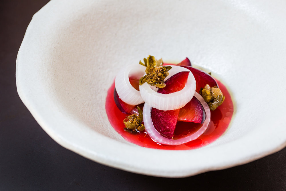 fermented plums, onions and fried capers dish