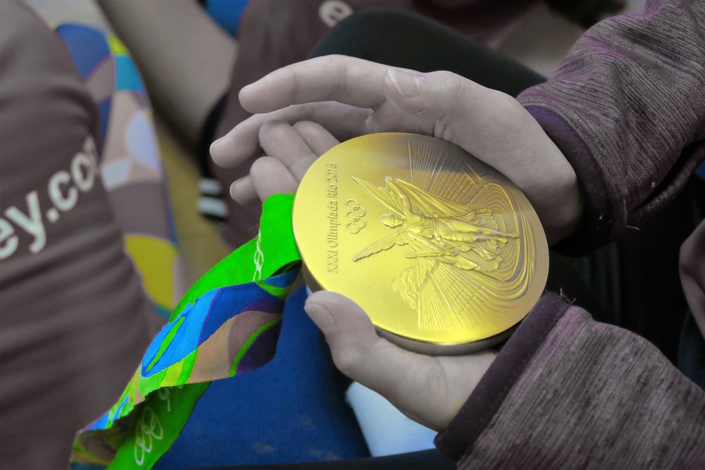 Rio 2016 Olympic gold medal being held by players at an EVO Hockey event
